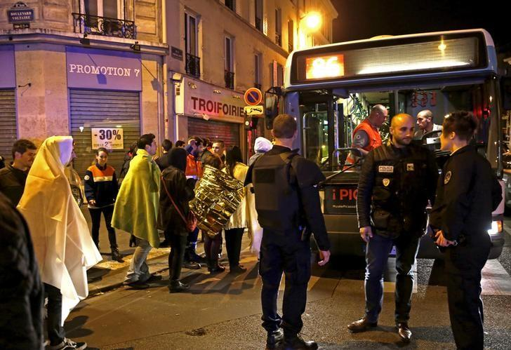 French police stand near people warming up on a street before being evacuated by bus near the Bataclan concert hall following fatal attacks in Paris, France, November 14, 2015. REUTERS/Philippe Wojazer/Files