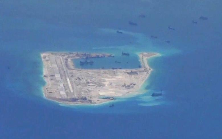 FILE PHOTO: Chinese dredging vessels are purportedly seen in the waters around Fiery Cross Reef in the disputed Spratly Islands in the South China Sea in this still image from video taken by a P-8A Poseidon surveillance aircraft provided by the United States Navy May 21, 2015. REUTERS/U.S. Navy/Handout via Reuters