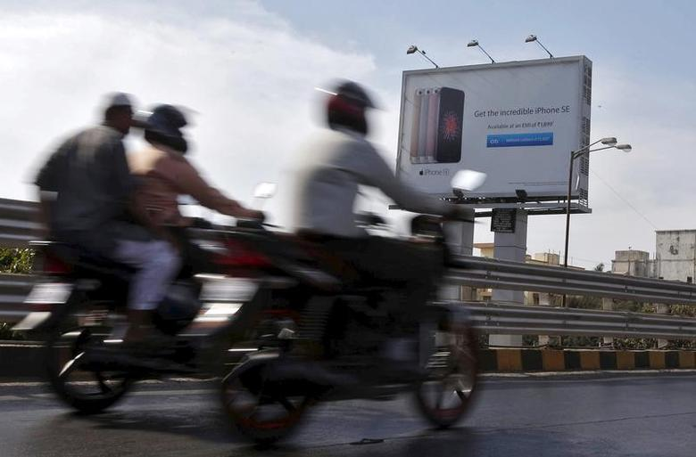 Men ride on motorbikes past an Apple iPhone SE advertisement billboard in Mumbai, India, April 26, 2016.  REUTERS/Shailesh Andrade - RTX2BSZS