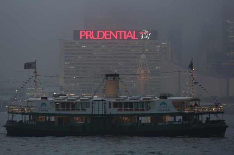 FILE PHOTO -  A ferry sails past an advertisement of Prudential Assurance under foggy weather at the Victoria Harbour in Hong Kong, China March 9, 2016. REUTERS/Bobby Yip/File Photo