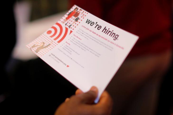 A job seeker holds a ''We're Hiring'' card while talking to a representative from Target at a City of Boston Neighborhood Career Fair on May Day in Boston, Massachusetts, U.S., May 1, 2017.   REUTERS/Brian Snyder/Files