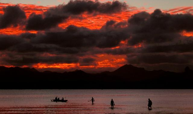 FILE PHOTO: A Fijian family board their canoe as sunset lights up the sky behind an island's mountain range in Suva May 1, 2004. REUTERS/David Gray/File Photo