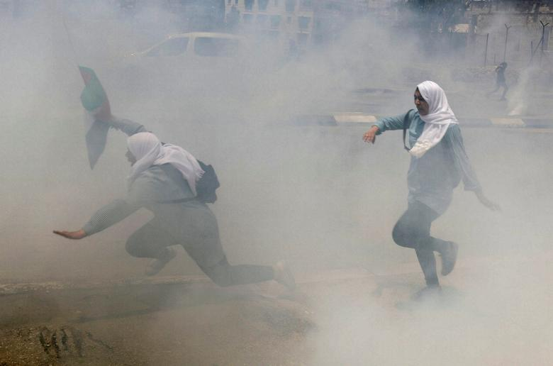 Palestinian school girls run for cover from tear gas fired by Israeli troops during clashes at a protest marking the 69th anniversary of Nakba, in the West Bank town of Bethlehem May 15, 2017. REUTERS/Ammar Awad