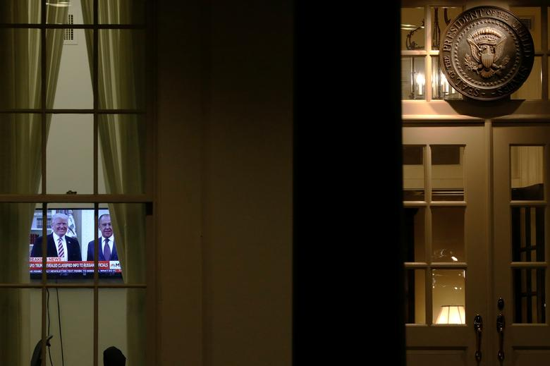 A television plays a news report on U.S. President Donald Trump's recent Oval Office meeting with Russia's Foreign Minister Sergei Lavrov as night falls on offices and the entrance of the West Wing White House in Washington, U.S. May 15, 2017. REUTERS/Jonathan Ernst