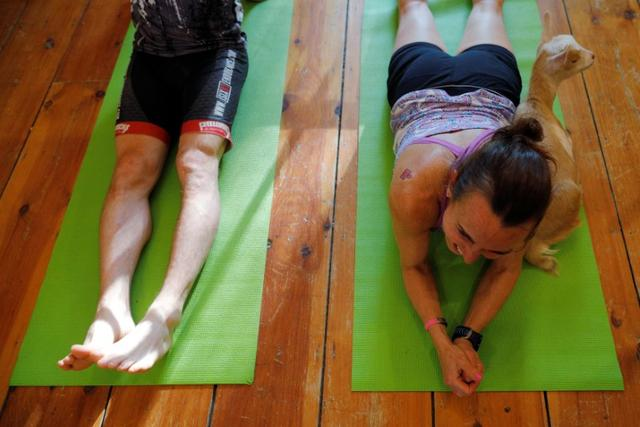 A goat lies next to Dawn Cobak at the conclusion of a yoga class with eight students and five goats at Jenness Farm in Nottingham, New Hampshire, U.S., May 18, 2017.  Picture taken May 18, 2017.    REUTERS/Brian Snyder