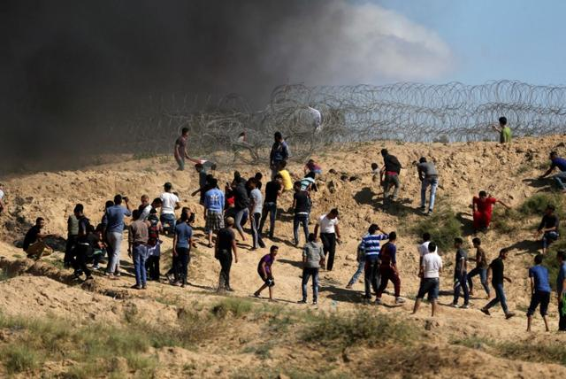 Palestinian protesters hurl stones at Israeli troops following a protest against the blockade on Gaza, near the border between Israel and Central Gaza Strip May 19, 2017. REUTERS/Ibraheem Abu Mustafa
