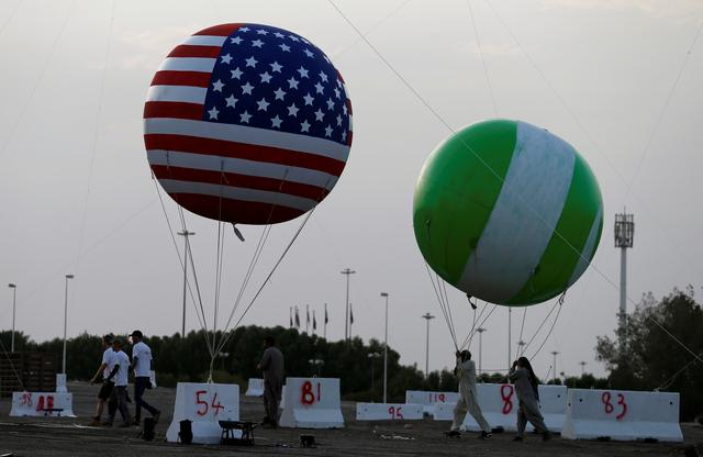 Workers are seen near a balloon with a United States flag on it as part of welcome celebrations ahead of the visit of U.S. President Donald Trump, in Riyadh, Saudi Arabia May 19, 2017. REUTERS/Hamad I Mohammed