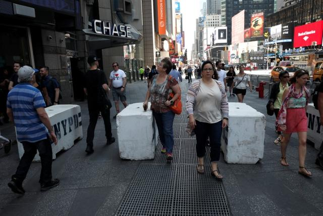 People walk between newly erected concrete barricades outside the 3 Times Square building in Times Square where a speeding vehicle struck pedestrians Thursday in New York City, U.S., May 19, 2017. REUTERS/Mike Segar