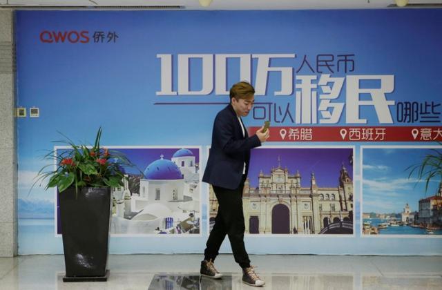 5月12日、トランプ米大統領の娘婿で上級顧問のジャレッド・クシュナー氏の親族企業が、同氏の名前を投資勧誘の際に利用したことを謝罪するなか、中国の移民仲介業者、僑外集団は、自らがこのプロジェクトにかかわっていることを大きく宣伝していた。写真は10日、北京に貼られた僑外集団のポスたの前を歩く男性(2017年 ロイター/Jason Lee)