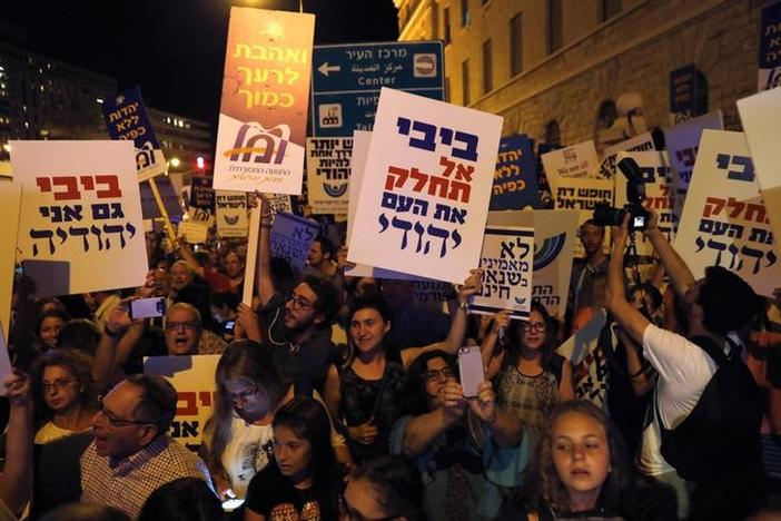 Protesters demonstrate against Benjamin Netanyahu's decision to go back on an agreement giving secular Jews equal prayer space to Orthodox worshipers at Jerusalem's Western Wall. Their placards, using the nickname for the Israeli prime minister, carried messages like 'Bibi, do not divide the Jewish People' and 'Bibi, I'm also a Jew.' July 1, 2017. Ronen Zvulun