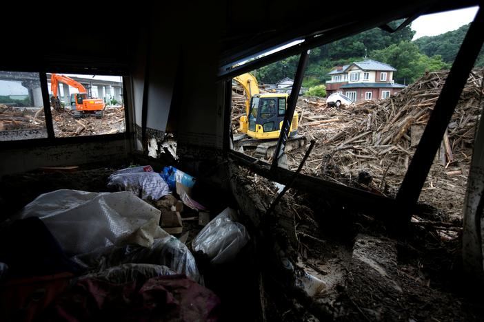 Workers use extravators to remove debris which were swept away by heavy rain in Asakura, Fukuoka Prefecture, Japan July 9, 2017. Issei Kato