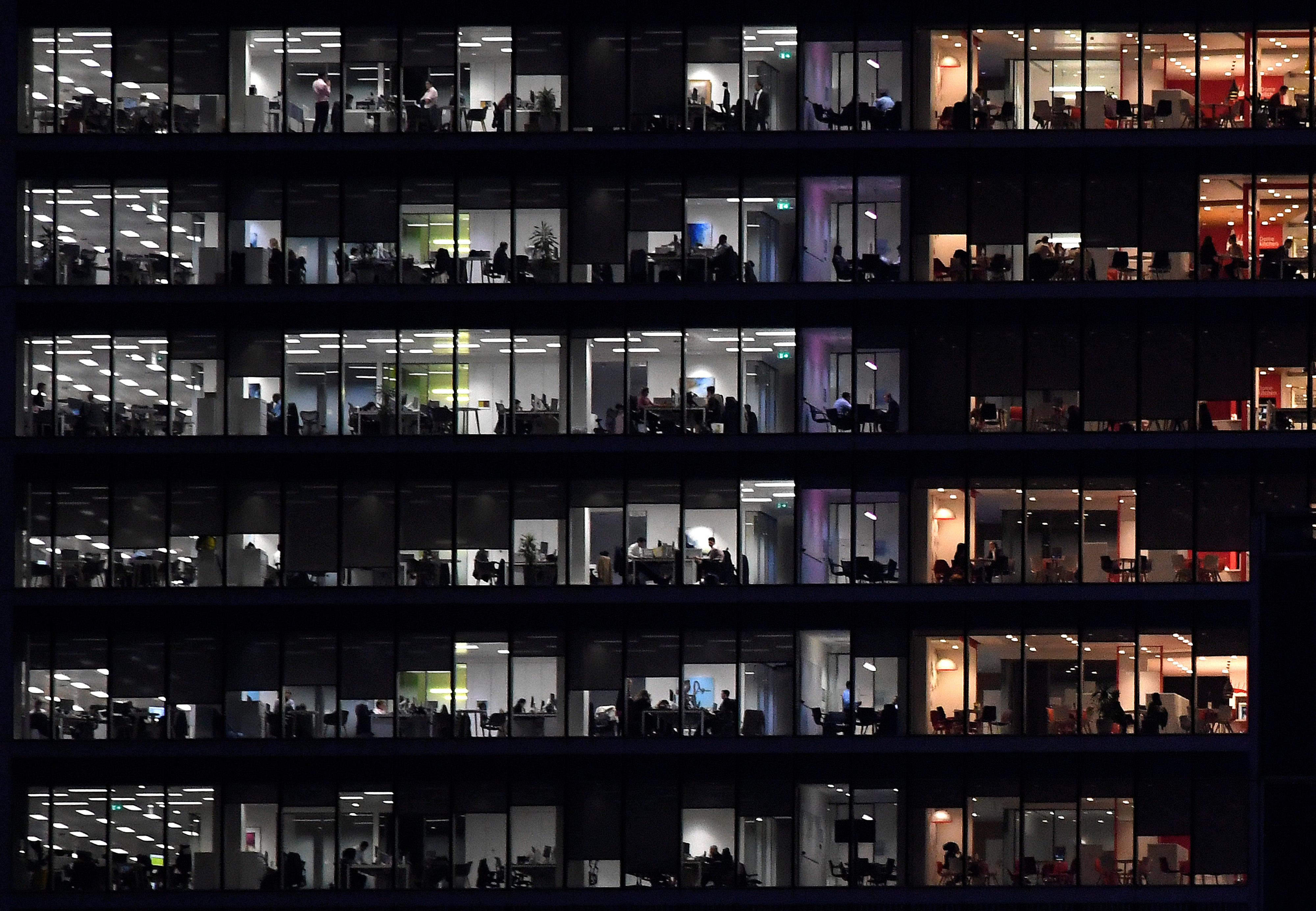 Workers in an office tower in the Canary Wharf financial district at dusk in London, November 17, 2017. The impact of the 2007-2008 financial crisis was particularly severe in Britain. Toby Melville