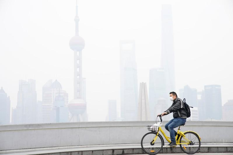 A man wearing a face mask rides a bicycle on a bridge in front of the financial district of Pudong covered in smog during a polluted day in Shanghai, China November 22, 2017. Aly Song