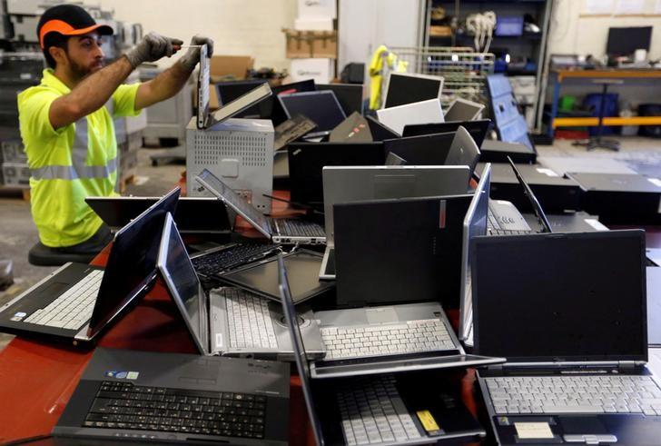 A worker at the Ecomicro recycling company dismantles computers in Saint-Loubes near Bordeaux, France October 16, 2017. Regis Duvignau