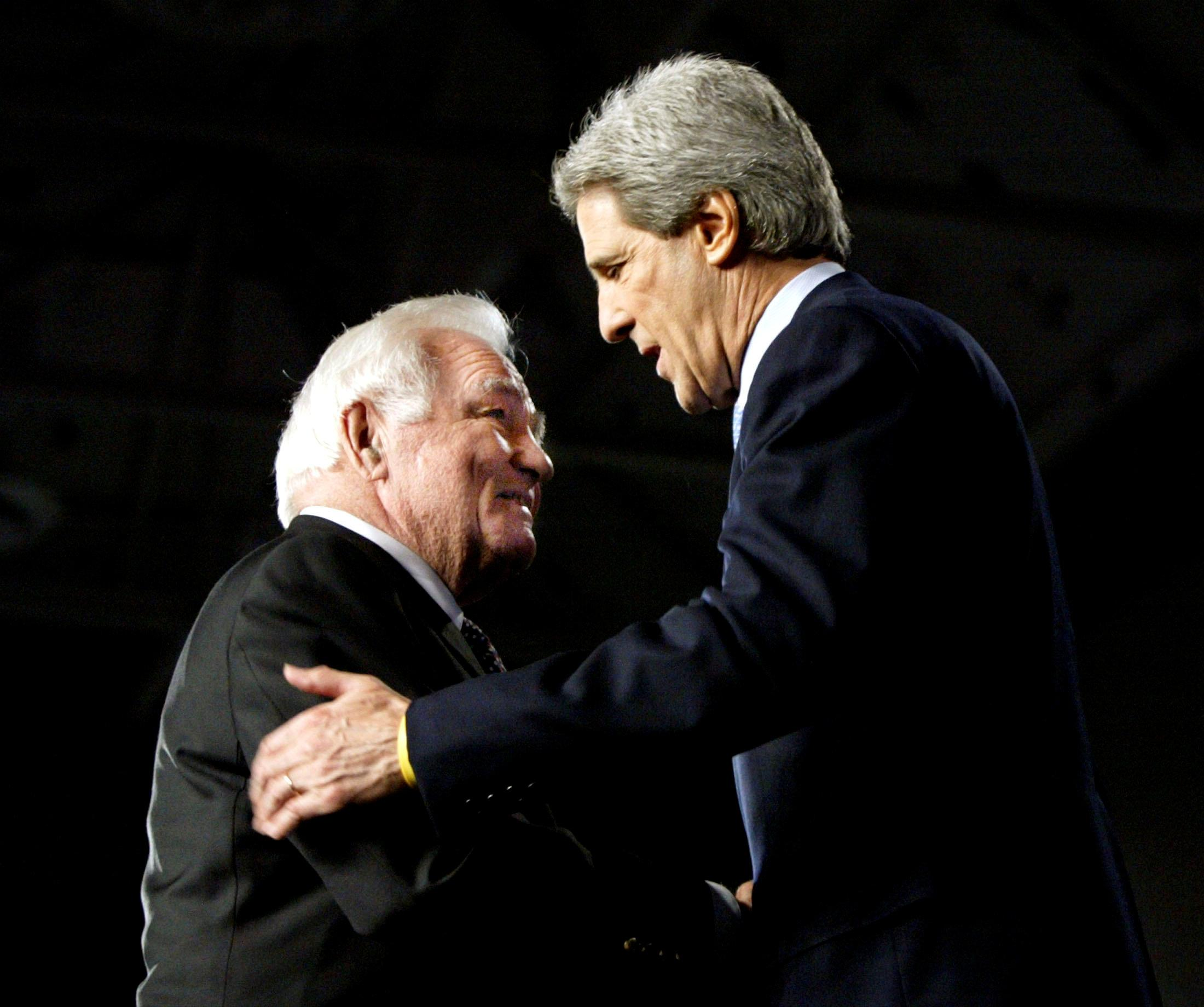 Retired Admiral Stansfield Turner (L) shakes hands with Democratic presidential nominee John Kerry after introducing Kerry in Waterloo, Iowa October 20, 2004. Brian Snyder