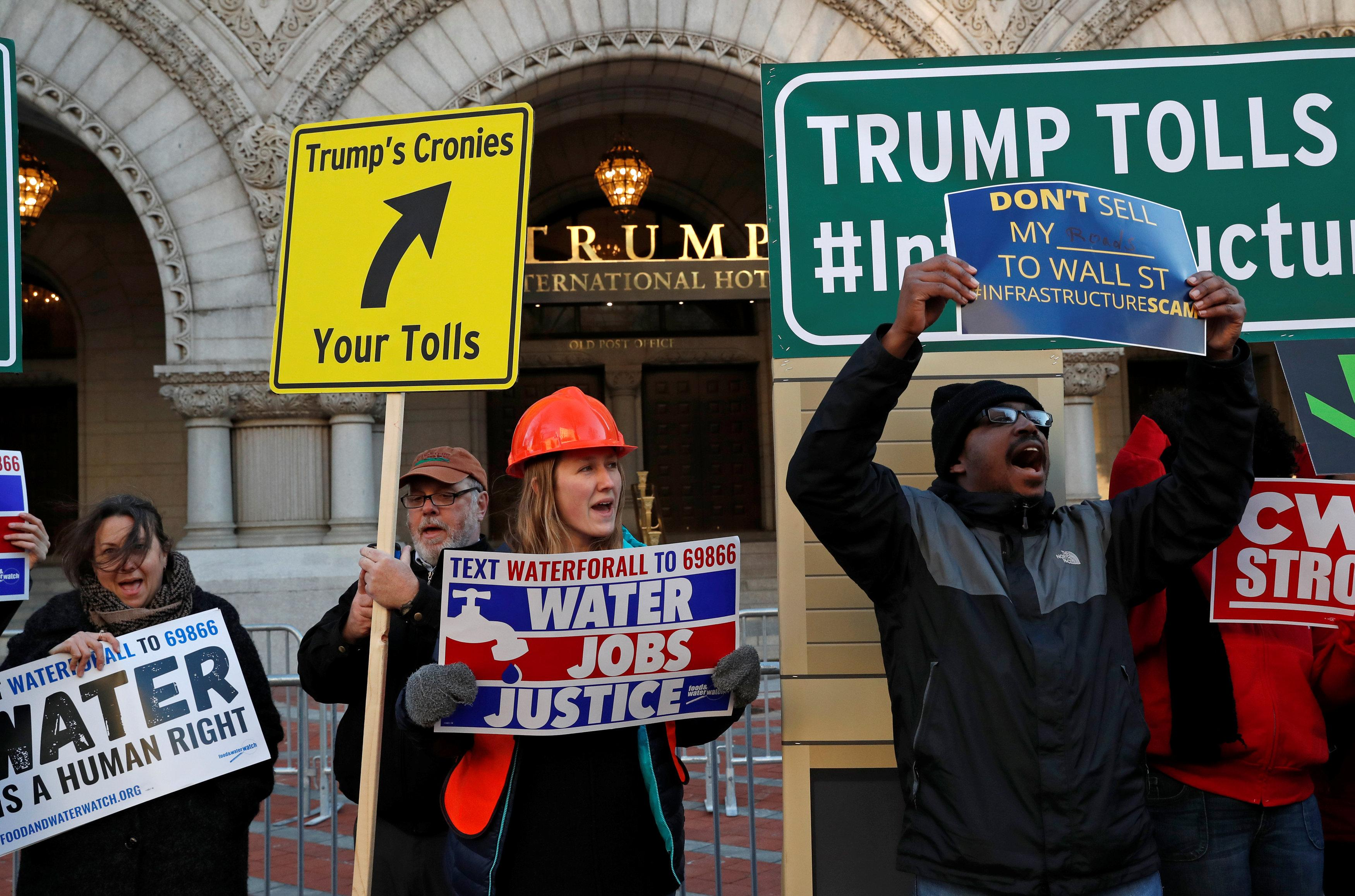 From left, Patty Lovera, Marty Hayden, Meg Robbins, and Dominic Lyon protest with others about U.S. President Donald Trump's recently unveiled infrastructure plan outside of the Trump International Hotel in Washington, U.S., February 12, 2018.  Leah Millis