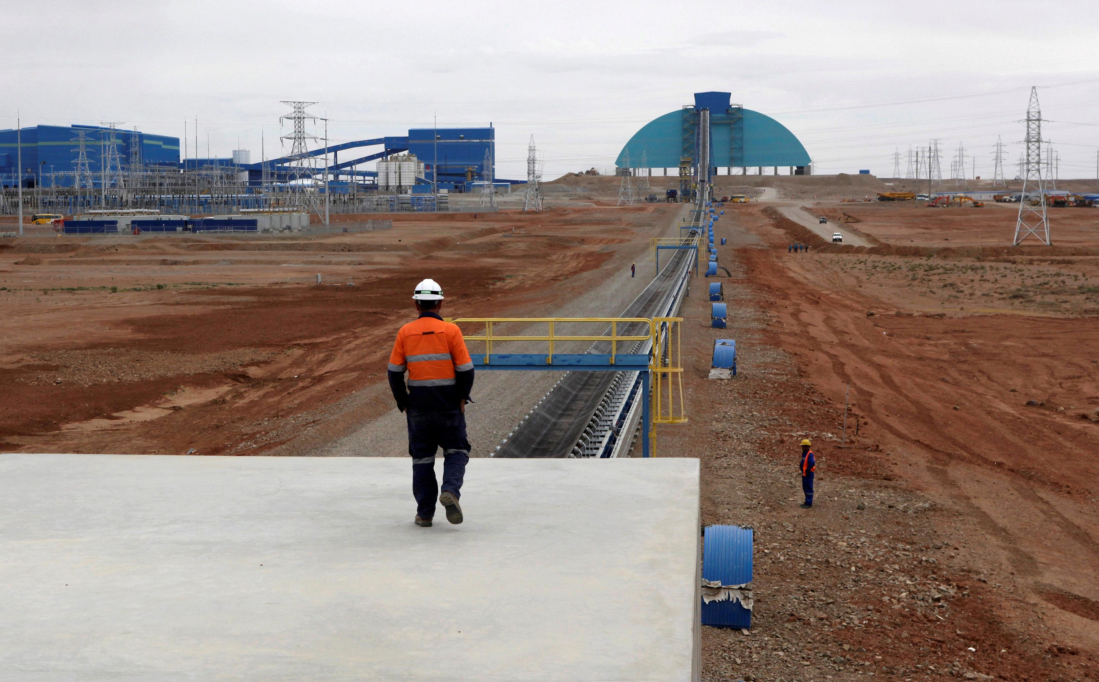 An employee looks at the Oyu Tolgoi mine in Mongolia's South Gobi region June 23, 2012. David Stanway