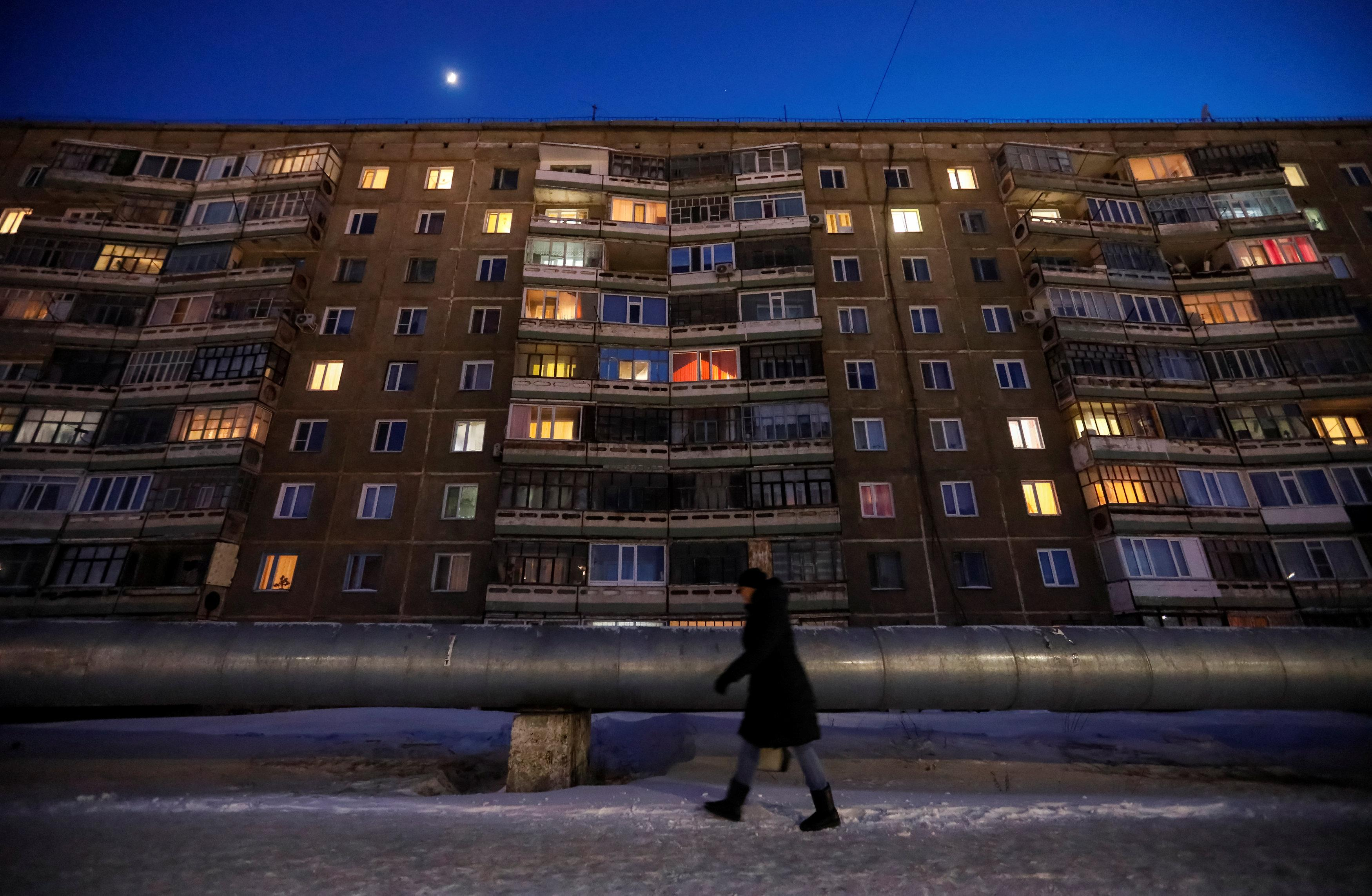 A woman walks past an apartment in the town of Aksu, north-eastern Kazakhstan, February 22, 2018.  Shamil Zhumatov