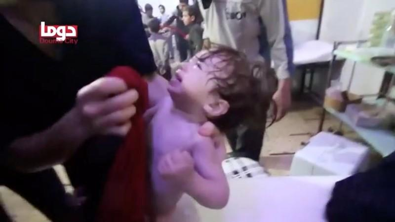 A child cries as its face is wiped following a chemical weapons attack in Douma, Syria in this still image from video obtained by Reuters on April 8, 2018. White Helmets/Reuters TV