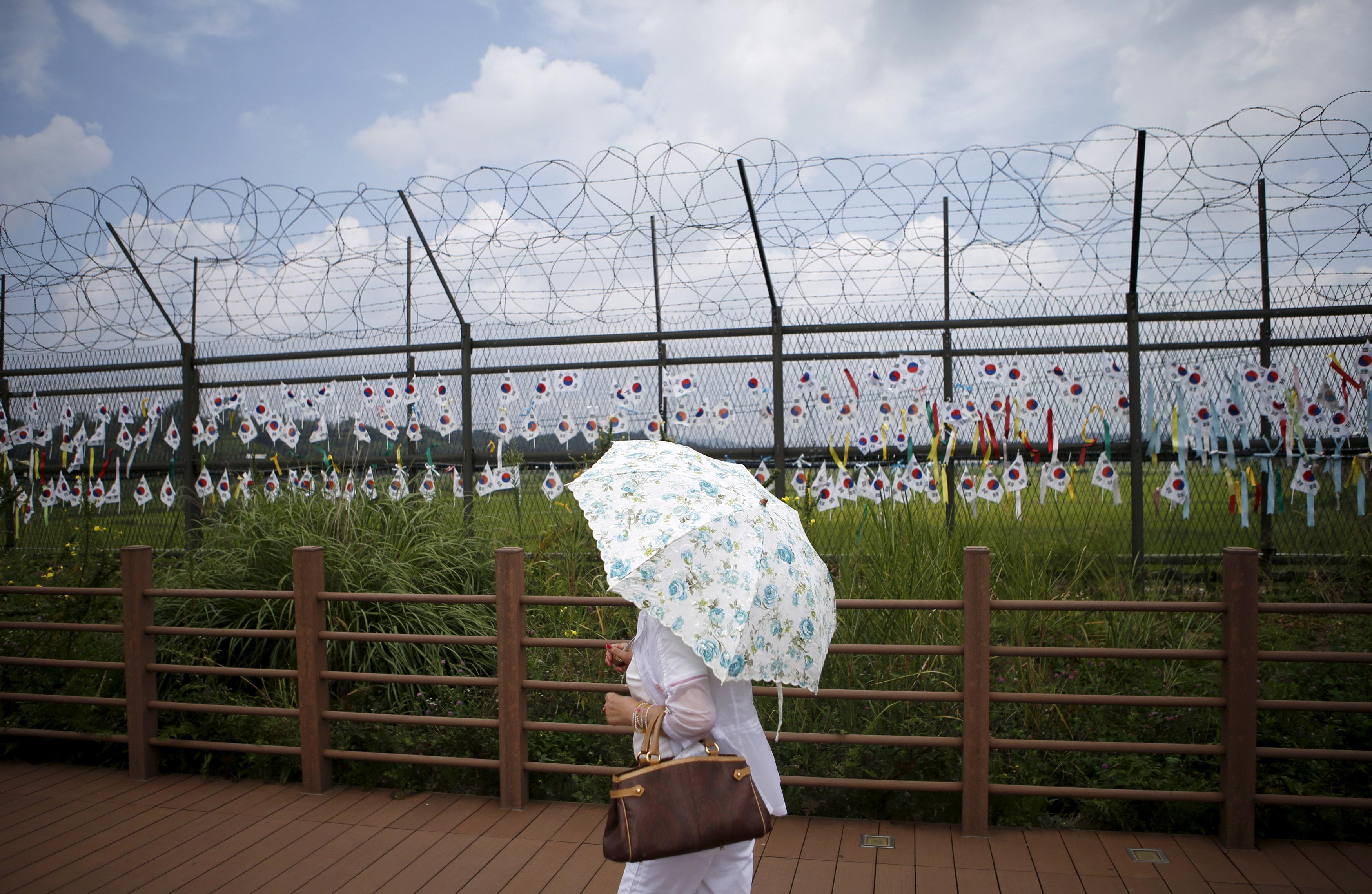 A tourist holding a parasol walks by a barbed-wire fence decorated by South Korean national flags at the Imjingak pavilion near the demilitarized zone separating the two Koreas in Paju, South Korea, August 22, 2015.  Kim Hong-Ji