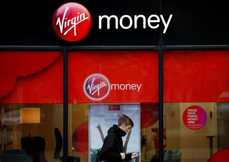 A man checks his phone as he walks past a branch of Virgin Money in Manchester, Britain September 21, 2017