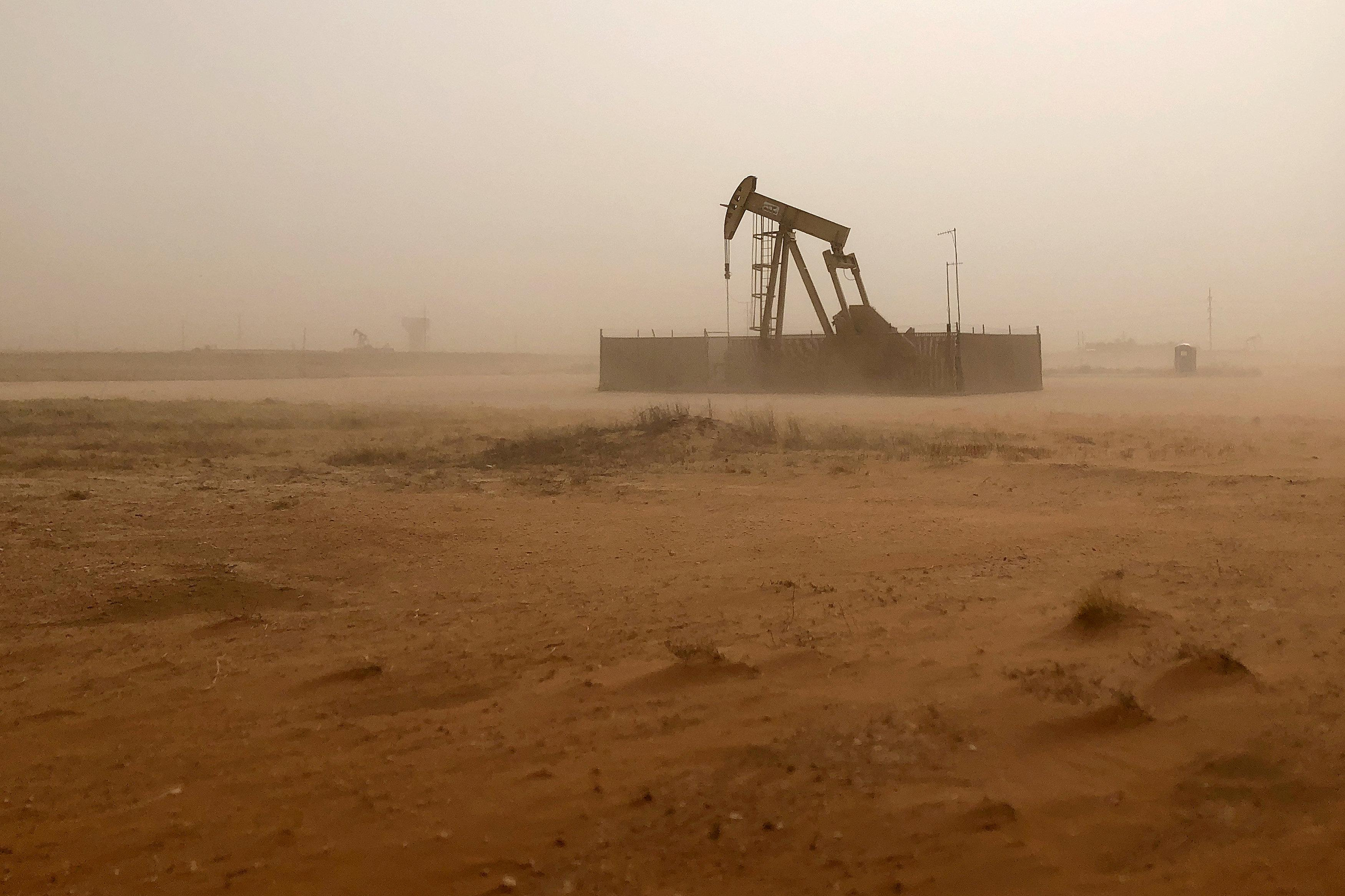 A pump jack lifts oil out of a well, during a sandstorm in Midland, Texas, U.S., April 13, 2018.    Ann Saphir