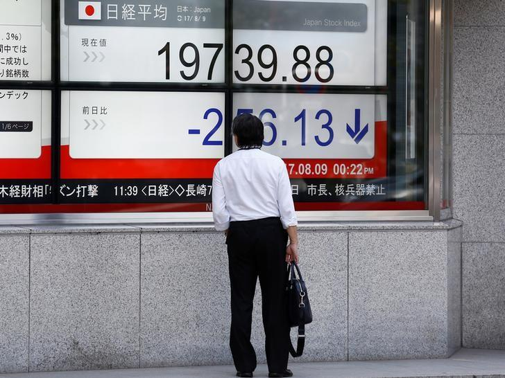 A man looks at an electronic board showing Japan's Nikkei average outside a brokerage at a business district in Tokyo, Japan August 9, 2017.   Kim Kyung-Hoon
