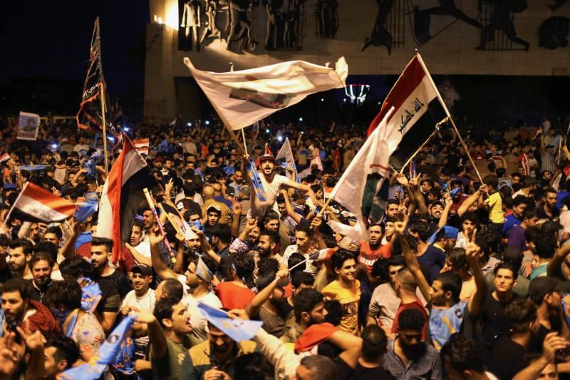 Iraqi supporters of populist cleric Moqtada al-Sadr celebrate after the results of Iraq's parliamentary election were announced in Baghdad, May 14, 2018. Thaier al-Sudani