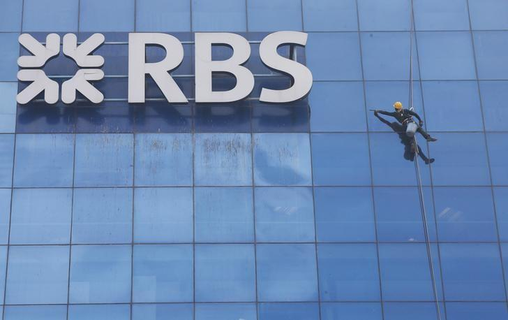 A worker cleans the glass exterior next to the logo of RBS (Royal Bank of Scotland) bank at a building in Gurugram on the outskirts of New Delhi, India, September 8, 2017. Adnan Abidi