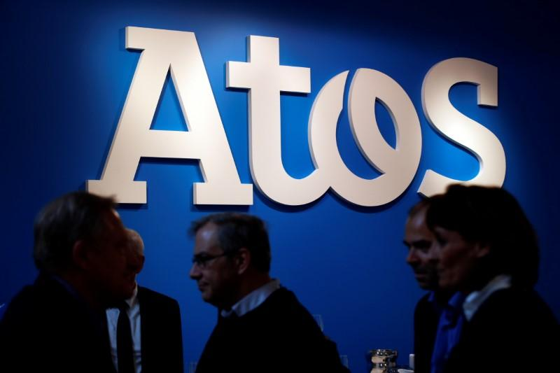 People walk in front of Atos company's logo during a presentation of the new Bull sequana supercomputer in Paris, France, April 12, 2016. Philippe Wojazer