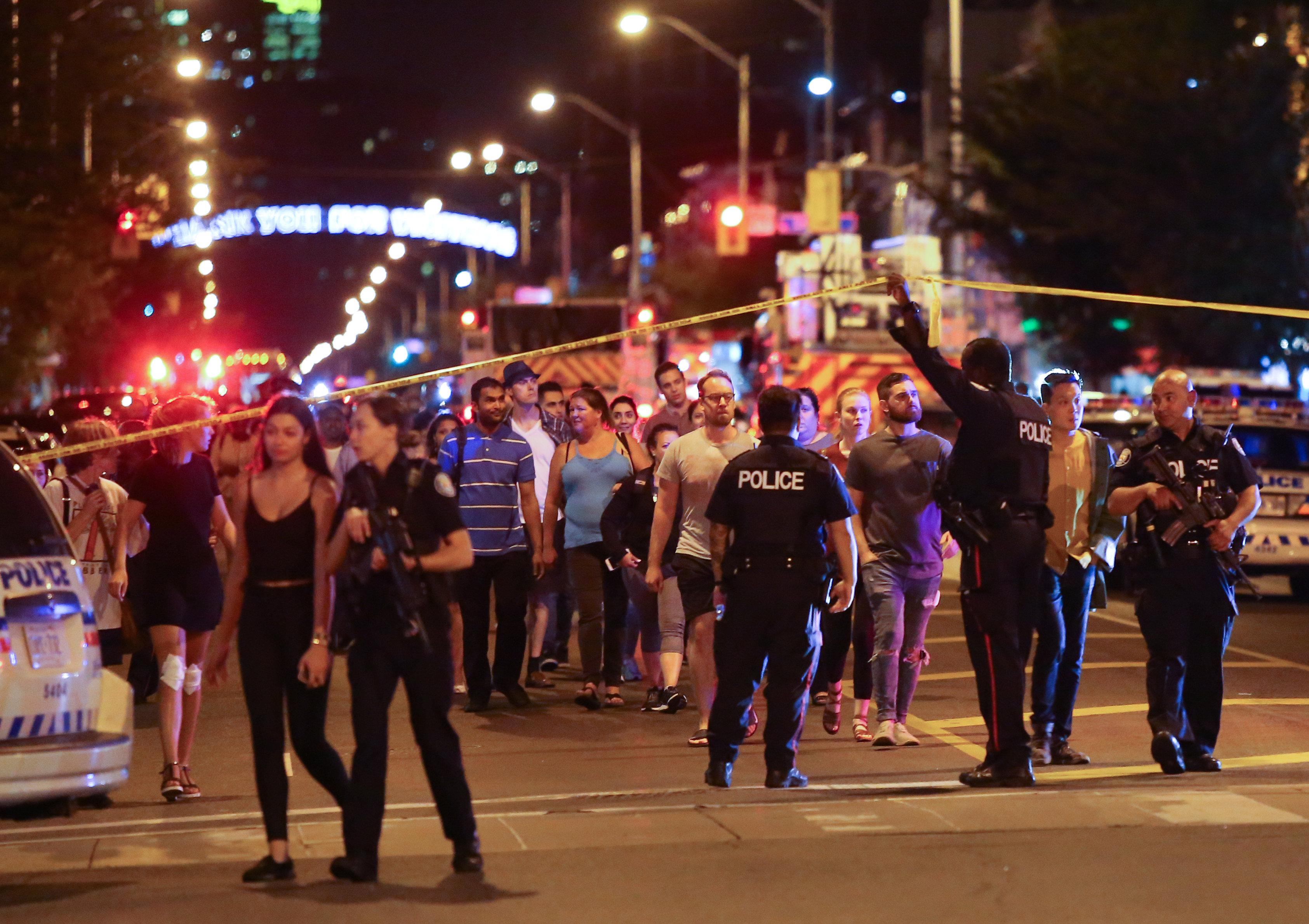 People leave an area taped off by the police near the scene of a mass shooting in Toronto, Canada, July 22, 2018. Chris Helgren