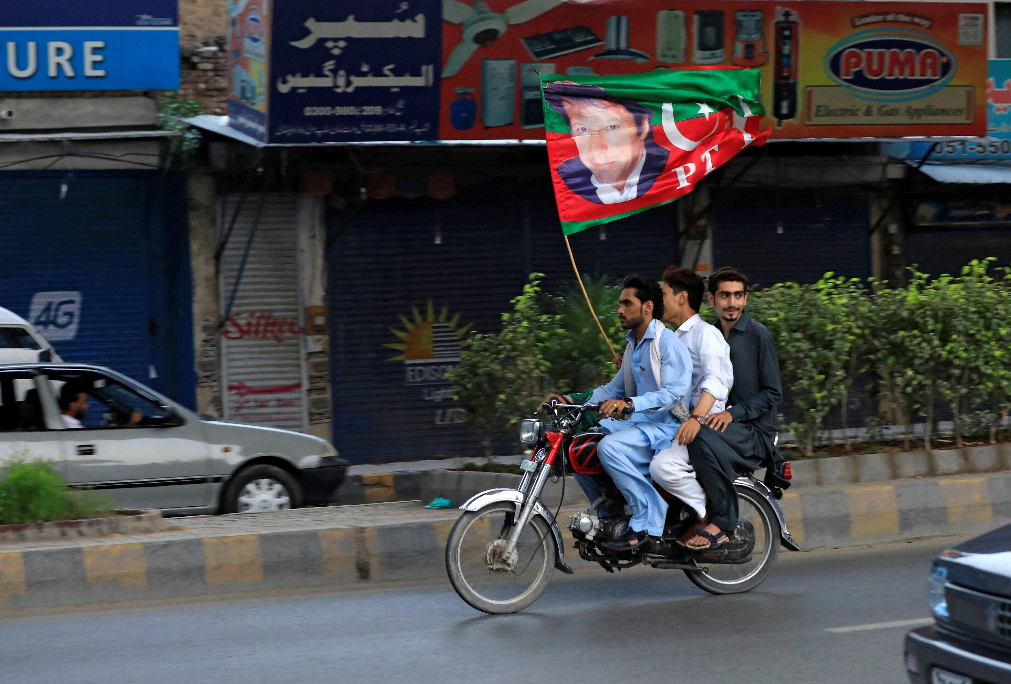 Supporters of Imran Khan, chairman of the Pakistan Tehreek-e-Insaf (PTI), political party wave a party flag as they celebrate during the general election in Rawalpindi, Pakistan July 25, 2018. Faisal Mahmood