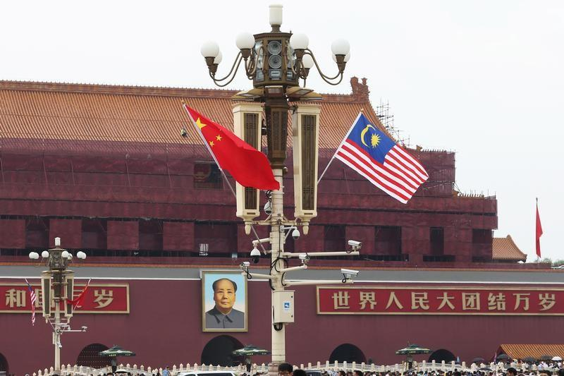 A Malaysian flag flutters next to a Chinese flag (L) as Malaysian Prime Minister Mahathir Mohamad visits China, at Tiananmen Square in Beijing, China August 19, 2018. Stringer