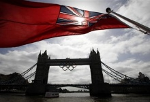 A flag on the back of a river boat flutters above Tower Bridge after the Olympic Rings were lowered into position for display from the walkways in central London, June 27, 2012. REUTERS/Andrew Winning