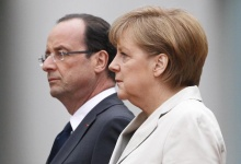 German Chancellor Angela Merkel and French President Francois Hollande listen to national anthems during a ceremony at the Chancellery in Berlin, May 15, 2012. REUTERS/Thomas Peter