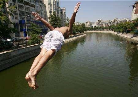 A boy jumps into Dambovita river on a hot day in central Bucharest, Romania July 18, 2007. REUTERS/Bogdan Cristel