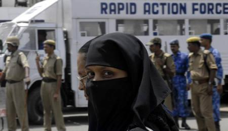 A veiled Muslim woman walks past policemen in Hyderabad August 10, 2007. Security in the city was beefed up after Muslim protesters assaulted exiled Bangladeshi author Taslima Nasreen at a book launch on Thursday. REUTERS/Krishnendu Halder