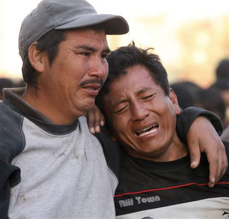 Men cry over their dead relatives in Pisco, some 152 miles south of Lima, August 16, 2007. Peruvians pulled hundreds of dead from the rubble of homes and churches on Thursday and  bodies piled up on street corners after a huge earthquake ravaged the country's central coast. REUTERS/Mariana Bazo