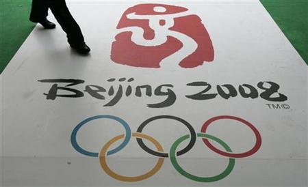 A man walks past the official logo for the 2008 Beijing Olympics during a countdown ceremony in Hong Kong March 27, 2007. China has warned of hijack threats during next year's Beijing Olympics in a country it says is increasingly infiltrated by international terrorists, state media reported on Tuesday. REUTERS/Bobby Yip