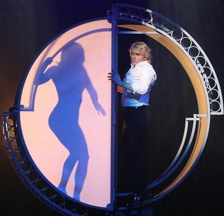 Dutch magician and illusionist Hans Klok performs on stage during a press preview before the start of his world tour in Cologne October 30, 2006. REUTERS/Michael Dalder