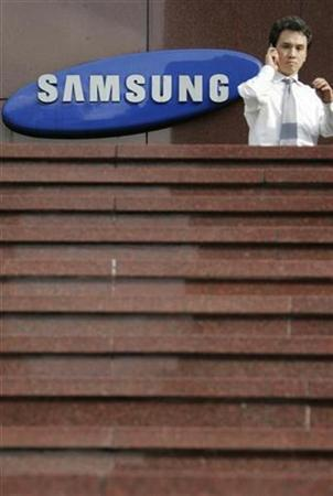 A man uses his mobile phone in front of Samsung Group's main office in Seoul, August 6, 2007. NXP will start shipping its single-chip solution for ultra-low-cost phones to Samsung from the fourth quarter of this year, Chief Executive Frans van Houten told Reuters on Friday. REUTERS/Lee Jae-Won