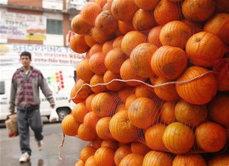 A shopper walks past oranges for sale in the Municipal Market in Asuncion August 10, 2007. Vitamin C can impede the growth of some types of tumors although not in the way some scientists had suspected, researchers reported on Monday. REUTERS/Jorge Adorno