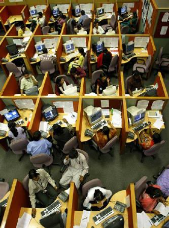 Employees seated in their cubicles at a call centre provide service support to international customers, in Bangalore in this March 17, 2004 file photo.  REUTERS/Sherwin Crasto