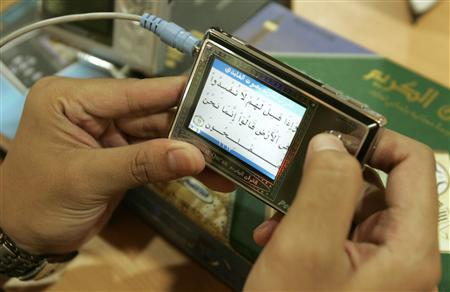 An Indonesian youth reads the Koran from a digital player at a book shop in Jakarta, September 20, 2007. REUTERS/Crack Palinggi