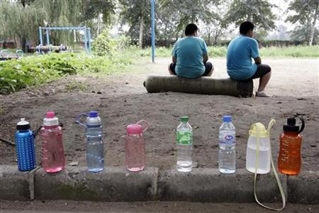 Drinking water bottles sit near two boys watching a game at OK Slim summer camp on the outskirts of Beijing August 3, 2006. Overweight children may show a collection of risk factors for heart disease by the time they are teenagers, a new study shows. REUTERS/Claro Cortes