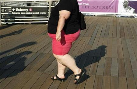 A woman walks along the boardwalk while leaving the U.S. Open tennis tournament in New York September 4, 2007. Obesity does not result simply from over-eating and a lack of exercise but is a consequence of modern life, a government think-tank said on Wednesday. REUTERS/Lucas Jackson