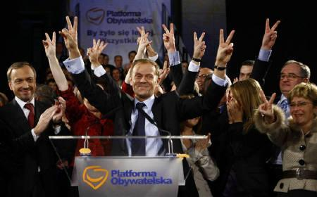 Donald Tusk, leader of the centre-right opposition party Platforma Obywatelska (Civic Platform) and his supporters flash victory signs as they celebrate their victory in Warsaw, October 21, 2007. REUTERS/Wolfgang Rattay