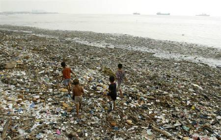 File photo of children walking along the polluted shoreline of Manila Bay October 9, 2007. REUTERS/John Javella/Files