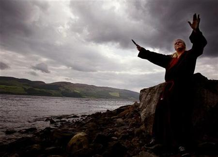 White witch Kevin Carlyon performs an invocation on the banks of Loch Ness in an attempt to summon the Loch Ness Monster, June 13, 2003. Witchcraft got its annual public outing on Wednesday with the celebrations surrounding Halloween when the occult comes into its own. REUTERS/Jeff J Mitchell