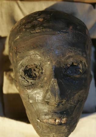The mummy of the boy pharaoh King Tutankhamun is displayed for the first time in public in a special climate-controlled glass showcase after it was taken out of its sarcophagus in Luxor's Valley of the Kings November 4, 2007. REUTERS/Nasser Nuri